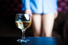Exponeringsglas av wine och naket lägger benen på ryggen Arkivbild