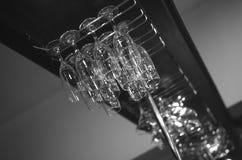 Exponeringsglas av wine Tomma exponeringsglas för vin Vinexponeringsglas i hylla ovanför en stång rack i restaurang Royaltyfri Foto