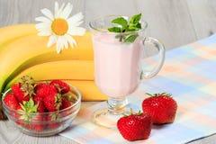 Exponeringsglas av yoghurt med mintkaramellen och nya jordgubbar, banan, chamo Arkivbilder