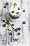 Exponeringsglas av yoghurt med nya blåbär Arkivbild