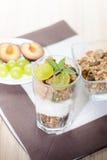 Exponeringsglas av yoghurt med sädesslag, frukt och mintkaramellen Royaltyfria Bilder