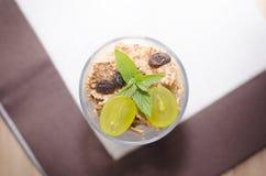 Exponeringsglas av yoghurt med sädesslag, frukt och mintkaramellen på en överkant arkivbilder