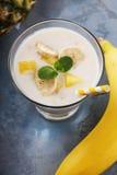 Exponeringsglas av yoghurt med stycken av banan och ananas Arkivfoton