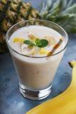 Exponeringsglas av yoghurt med stycken av banan och ananas Royaltyfri Bild