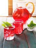 Exponeringsglas för bärkompottkaraff med äppleskivor på sol- trälantlig bakgrund Royaltyfria Bilder