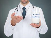 Exponeringsglas för doktor Holding Lactose Free av mjölkar arkivfoto