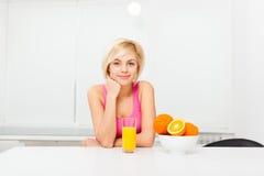 Exponeringsglas för drink för orange fruktsaft för kvinna i hennes kök royaltyfri foto