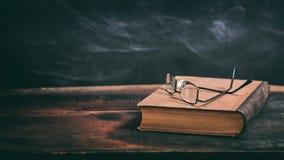 Exponeringsglas för gammal bok och ögonpå svart tavlabakgrund Royaltyfria Bilder