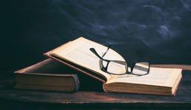 Exponeringsglas för gammal bok och ögonpå svart tavlabakgrund Fotografering för Bildbyråer