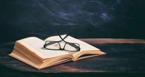 Exponeringsglas för gammal bok och ögonpå svart tavlabakgrund Royaltyfria Foton