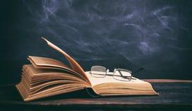 Exponeringsglas för gammal bok och ögonpå svart tavlabakgrund Royaltyfri Fotografi