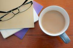 Exponeringsglas för kaffekopp och buntbokpå den röda wood tabellen Royaltyfri Bild
