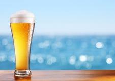 Exponeringsglas för kallt öl på stångtabellen på det frilufts- kafét royaltyfria bilder
