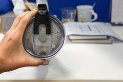 Exponeringsglas för kvinnahållvakuum med tänt överst för drink royaltyfria foton