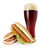 Exponeringsglas för mörkt öl och två varmkorvar med olika ingredienser royaltyfri foto