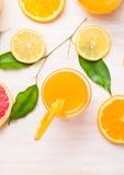 Exponeringsglas för orange fruktsaft med skivor av citrus- och gräsplansidor på vitt trä Royaltyfria Bilder