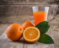 Exponeringsglas för orange fruktsaft och nya apelsiner Royaltyfria Bilder