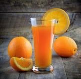 Exponeringsglas för orange fruktsaft och nya apelsiner Royaltyfri Foto