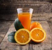 Exponeringsglas för orange fruktsaft och nya apelsiner på trä Royaltyfri Fotografi