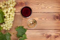 Exponeringsglas för rött och vitt vin och grupp av druvor Arkivbild