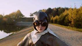 Exponeringsglas för tappning för lycklig liten rolig flygarepojke som bärande pilot- kör in mot kameran som låtsar för att vara e arkivfilmer