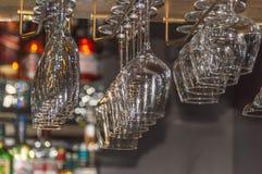 Exponeringsglas för vin, champagne, konjak på en special montering på den bästa hyllan av stången royaltyfri fotografi