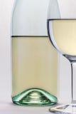Exponeringsglas för vitt vin och flaskcloseupen islolated på vit backgroun Arkivbild