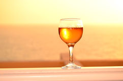 Exponeringsglas för vitt vin på en solnedgångbakgrund Royaltyfria Bilder