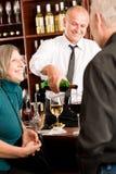 exponeringsglas för stångbartenderpar häller hög wine Royaltyfria Bilder
