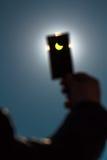 Exponeringsglas i handen som stänger den sol- förmörkelsen Arkivbild