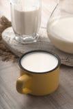 Exponeringsglas, kanna, gul kopp av kefir och servett på en vit tabell Royaltyfri Fotografi