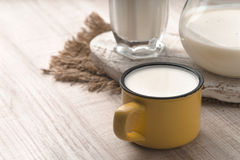 Exponeringsglas, kanna, kopp av kefir och servett på en vit tabell Royaltyfria Foton