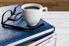 Exponeringsglas, kopp av varmt kaffe och bok på trätabellen Fotografering för Bildbyråer