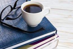 Exponeringsglas, kopp av varmt kaffe och bok på trätabellen Arkivbild