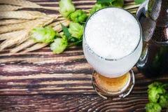 Exponeringsglas med öl med flygtur på en trätabell Royaltyfri Bild