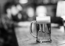 Exponeringsglas med öl på stångräknaren, tabell, besökare på bakgrund som är defocused Exponeringsglas med nytt lagerutkastöl med Arkivfoto