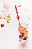 Exponeringsglas med bär lemonad, iskuber och rött sugrör på vit träbakgrund Royaltyfri Foto