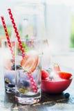 Exponeringsglas med bärlemonad med röda sugrör- och iskuber på köksbordet över trädgårds- bakgrund Royaltyfri Bild