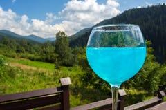 Exponeringsglas med blå champagne mot bakgrunden av bergen royaltyfria bilder