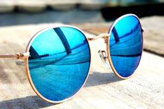 Exponeringsglas med blåa exponeringsglas på sollögnen på ett trägolv vilar turen reflekterad i ett exponeringsglas Arkivfoton