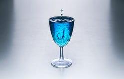 Exponeringsglas med blått vatten på en tabell Arkivfoto