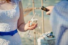 Exponeringsglas med champagne är i brudens händer Royaltyfri Fotografi