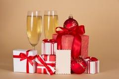 Exponeringsglas med champagne, julgåvor och leksaker arkivbild