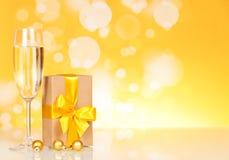 Exponeringsglas med champagne och en gåva arkivbild