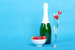 Exponeringsglas med champagne- och jordgubbeskivor bredvid en flaska av Royaltyfria Foton