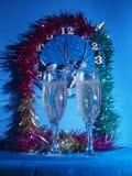 Exponeringsglas med champagne på bakgrunden av klockan övergående tid för klockadrömliv Arkivfoton