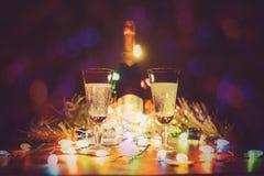 Exponeringsglas med champagne står på en trätabell Arkivfoton