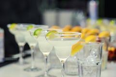 Exponeringsglas med coctailar, champagne, fruktsaft Exponeringsglas på viten ta Arkivfoto