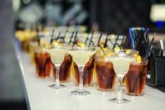 Exponeringsglas med coctailar, champagne, fruktsaft Exponeringsglas på viten ta Arkivbild