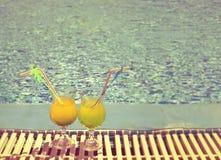 Exponeringsglas med coctailen på kanten av pölen, med en retro effekt royaltyfri fotografi